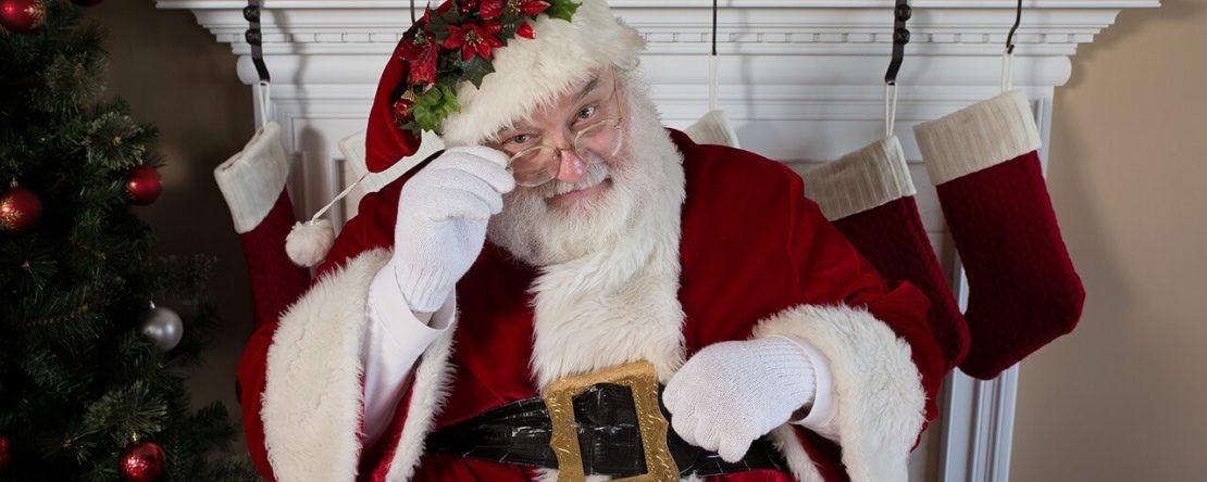 Санта Клаус що сидить біля каміну