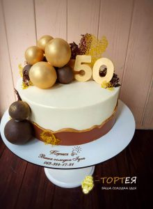 Торт оформлений золотими шоколадними кульками